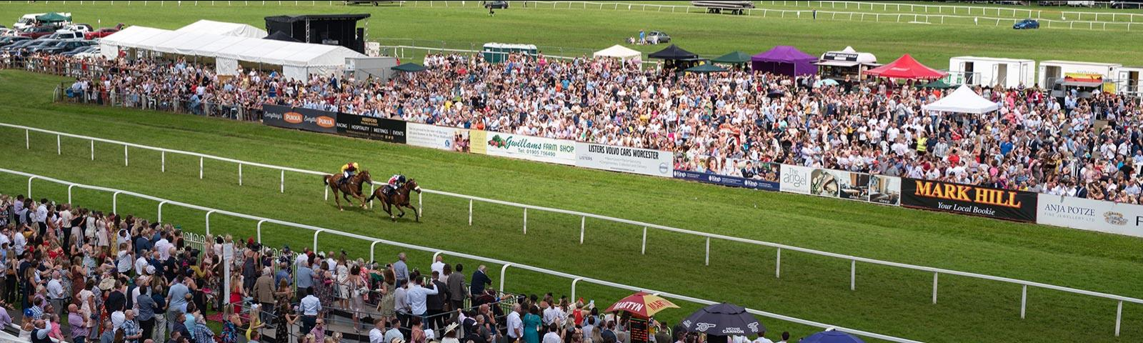 Crowds at Worcester Racecourse watching racing action.