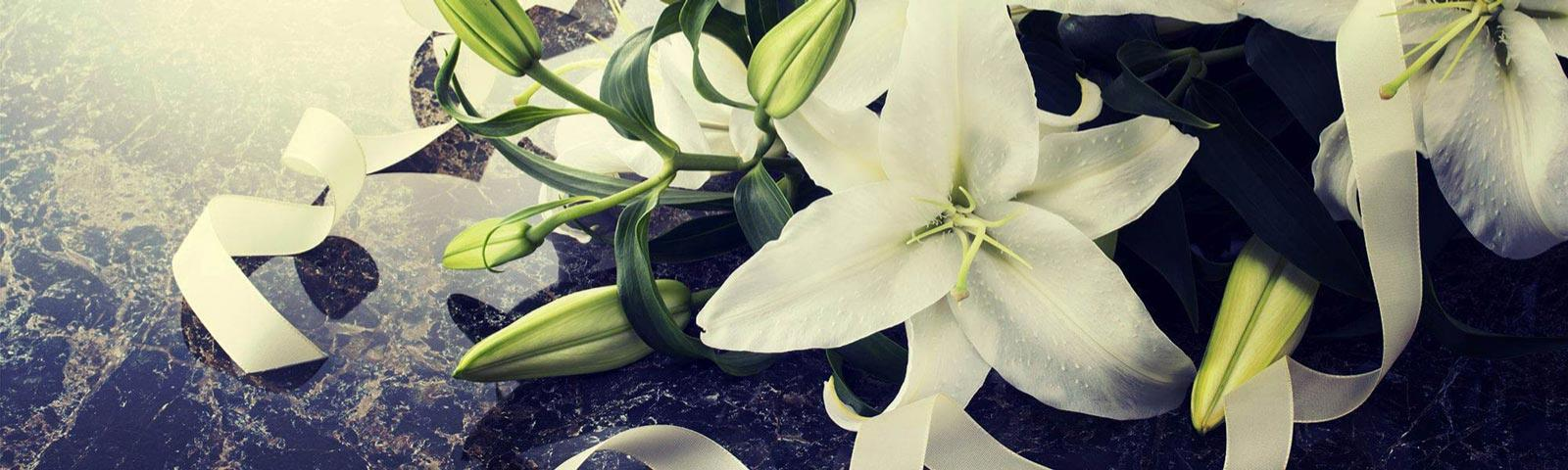 White lilies resting on a dark marble background.