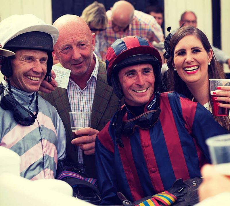Jockeys posing for a photo with racegoers.
