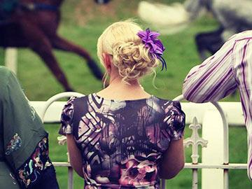 A dressed up woman at the races.