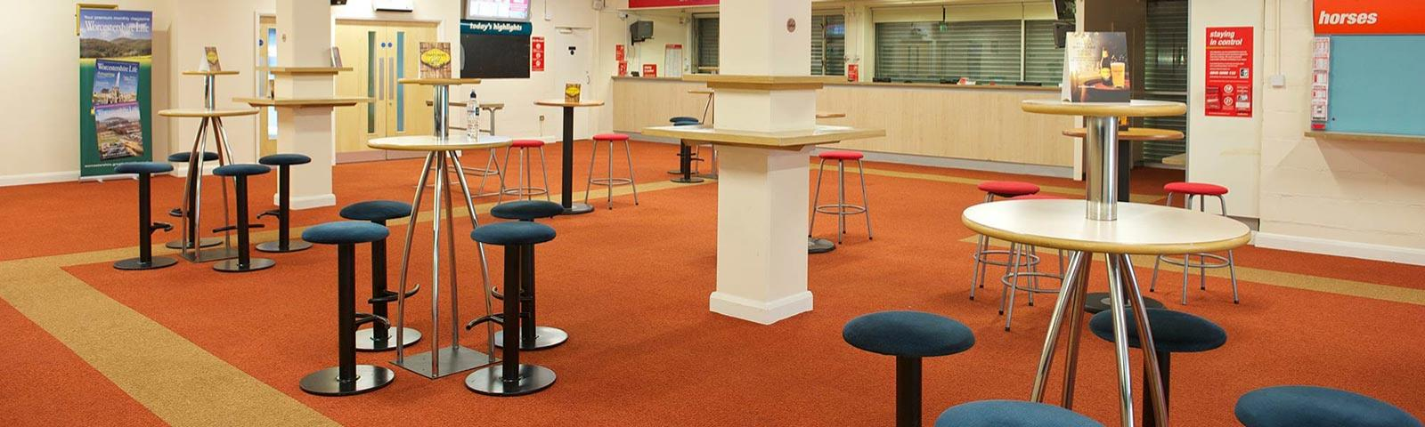 Several smaller round tables dotted around a bar area.