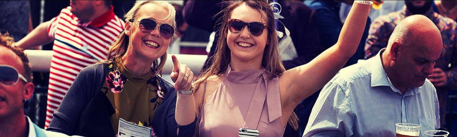 Two women attedning racing at Worcester Racecourse, smiling for a photo.