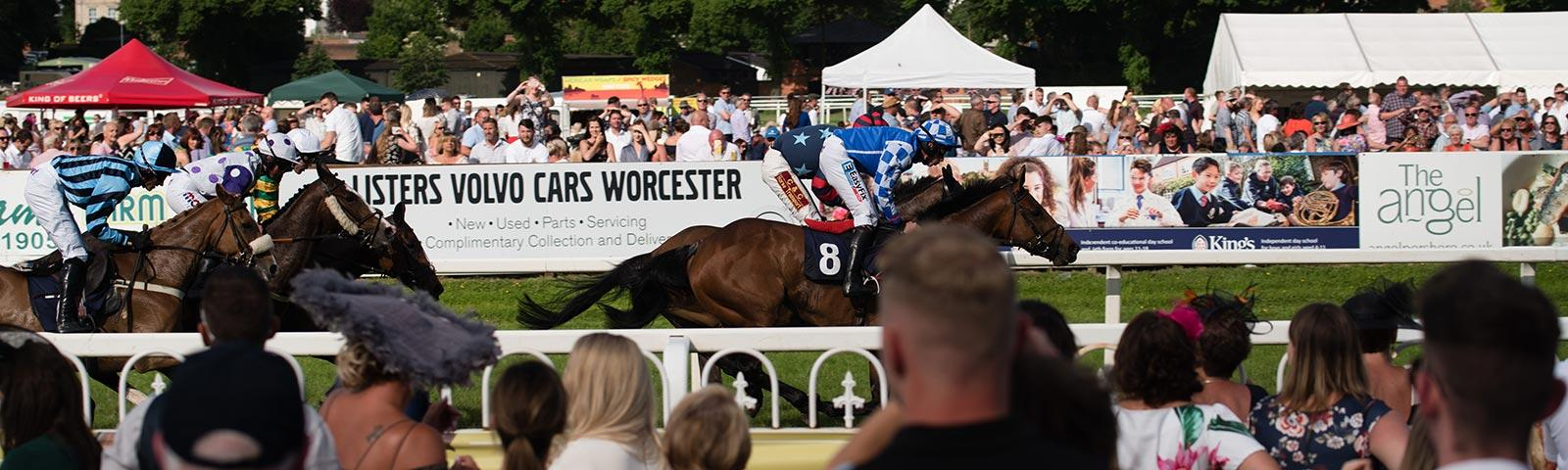 Crowds watching racing action at Worcester Racecourse.