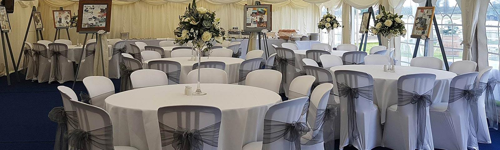 An array of large round tables decorated in white with flowers sat in the middle of each.  All inside our outdoor marquee.