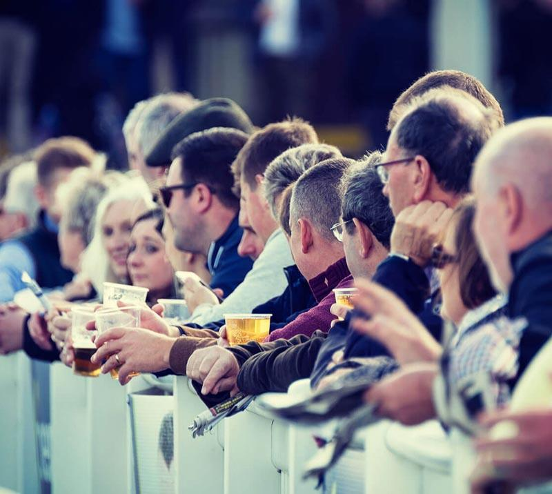 Crowds lined up next to the track at Worcester Racecourse.