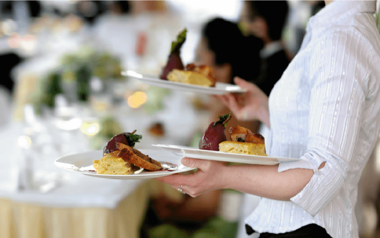 A member of waiting staff delivers starters