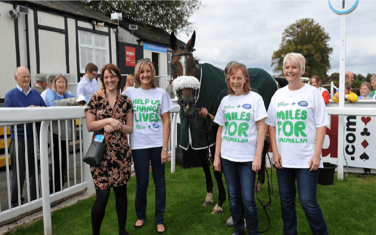 Ladies from Macmillan Cancer Support pose with a Racehorse promoting Worcester Racecourses 5th Annual Macmillan Raceday