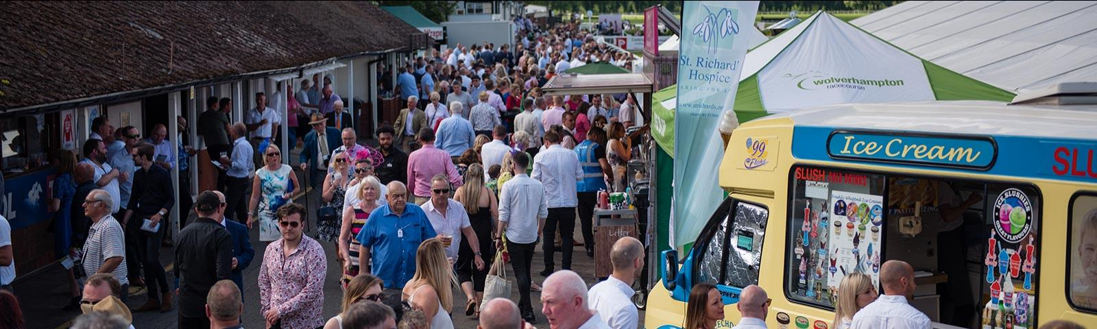 Crowds walking around Worcester Racecourse during an event.