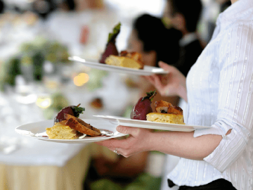 A member of waiting staff serves dessert.